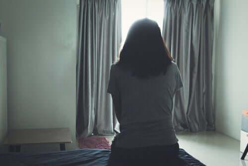 Donna che pensa seduta di spalle sul letto