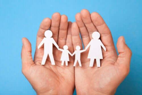 Mani sostengono famiglia fatta di sagome di carta