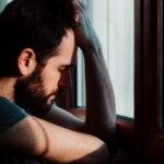 Uomo afflitto davanti alla finestra