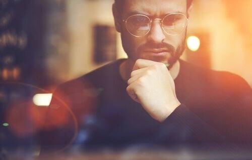 Uomo con occhiali pensieroso