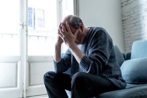 Uomo anziano seduto e preoccupato con le mani in testa