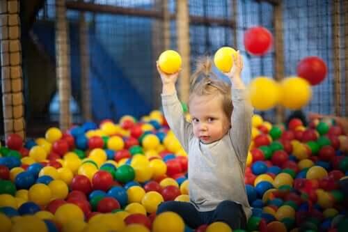 Psicomotricità per i bambini, bambina nel box con le palline