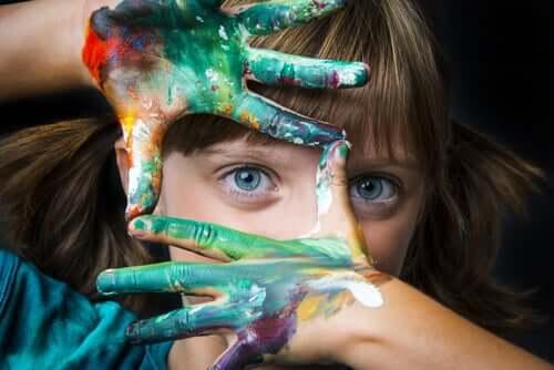 Bambina con le mani sporche di vernice