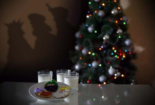 Albero di natale addobbato con luci e palle e dolci sulla tavola con bicchieri di latte