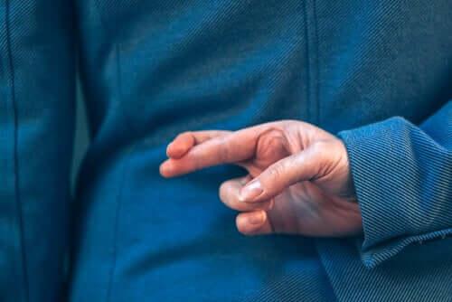 Come individuare l'inganno, uomo incrocia le dita dietro la schiena