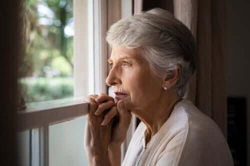 Donna che guarda dalla finestra con demenza corticale e sottocorticale