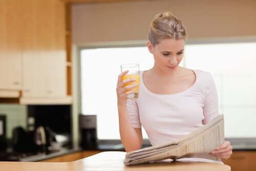 Donna con giornale e succo d'arancia