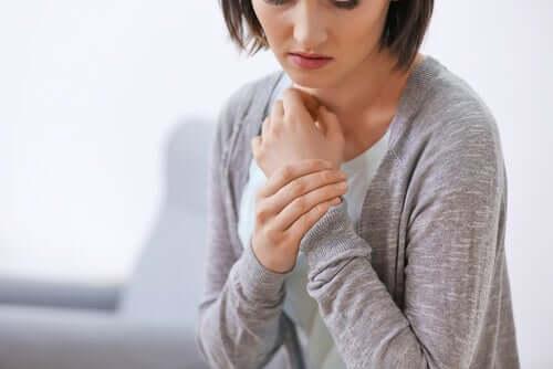 Donna che riflette mentre si tiene il polso