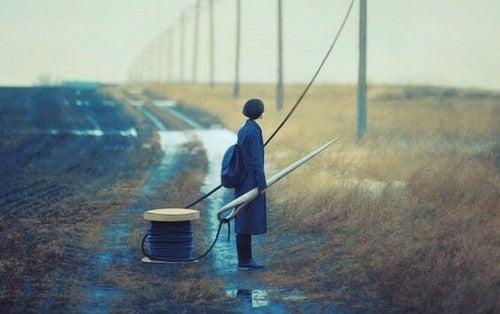 Ragazza in mezzo a un campo con ago e filo in mano simbolo di vittimismo e isolamento