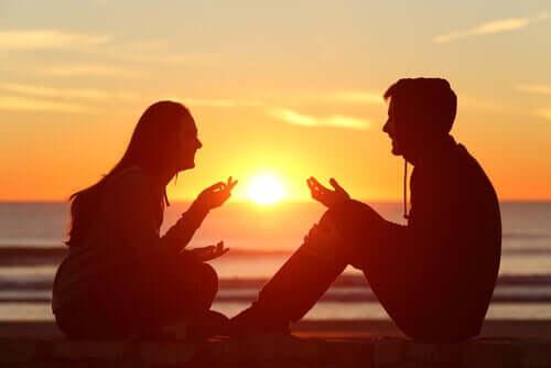 Coppia che ride insieme davanti al tramonto