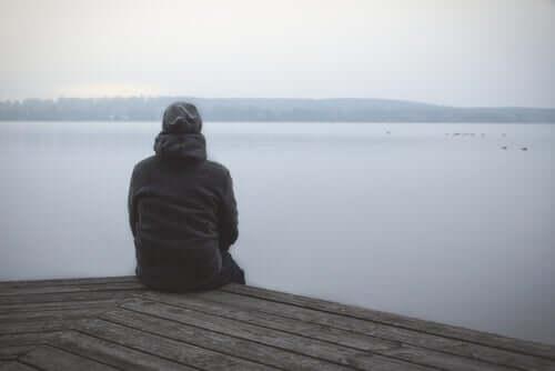 Uomo di spalle seduto di fronte al mare