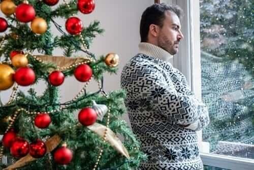 Uomo triste accanto all'albero di Natale