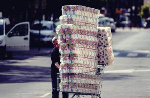 Uomo con il carrello pieno di carta igienica