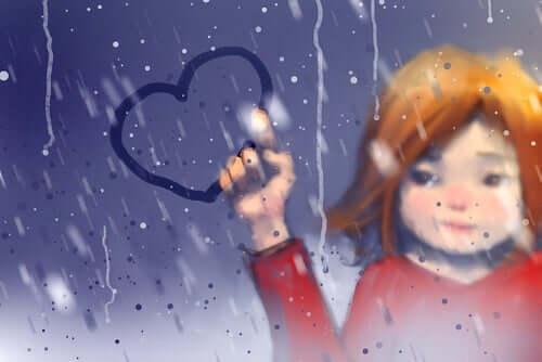Bambina che disegna un cuore sulla finestra appannata