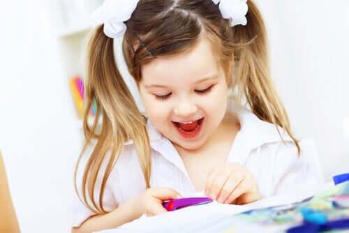 Bambina che si diverte mentre ritaglia un cartoncino