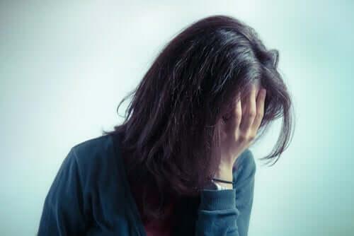 Donna ansiosa che si copre il viso con la mano