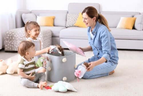 Madre raccoglie i giocattoli con i figli