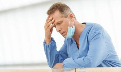 Medico pensieroso e afflitto e operatori sanitari al tempo del Coronavirus