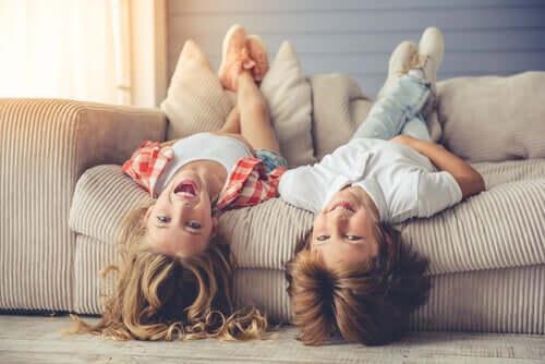 Bambini che giocano a testa in giù sul divano.