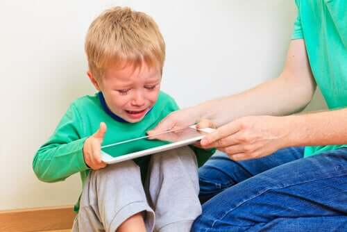 Mamma che dà il tablet al figlio che piange