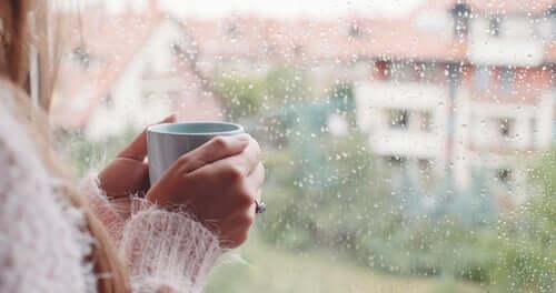 Donna con una tazza di caffè in mano che guarda dalla finestra