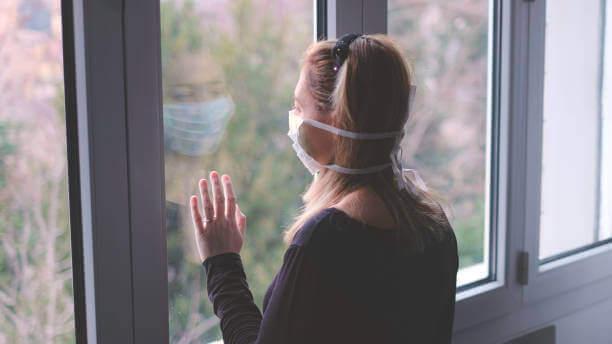 Donna con la mascherina alla finestra