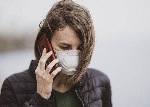 Donna con mascherina e cellulare