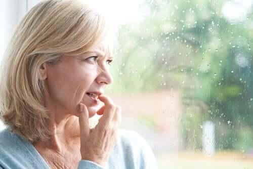 Donna preoccupata davanti alla finestra