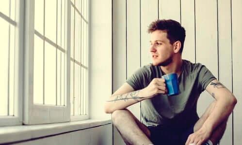 Ragazzo di fianco a una finestra che beve il caffè