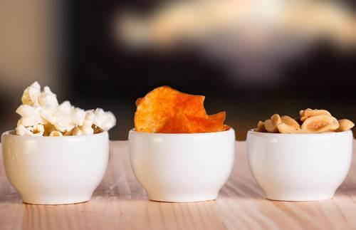 Ciotole con patatine, pop corn e arachidi