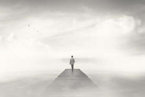 Uomo solo su un ponte in mezzo alla nebbia