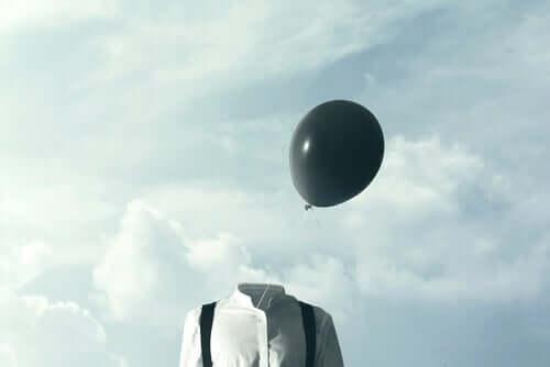 Uomo con palloncino nero al posto della testa
