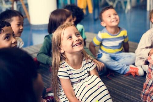 Bambini felici seduti per terra a scuola