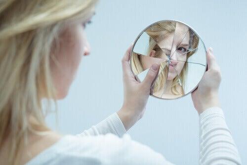 Delirio del vetro, donna davanti a specchio rotto