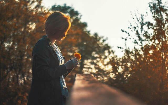 Donna con fiore arancione in mano
