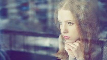 Donna pensierosa guarda alla finestra