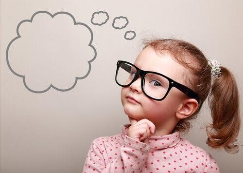 Bambina con gli occhiali che pensa