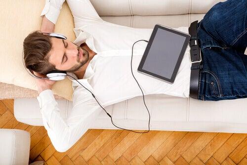 Ragazzo che ascolta musica sul divano durante il tempo in pandemia