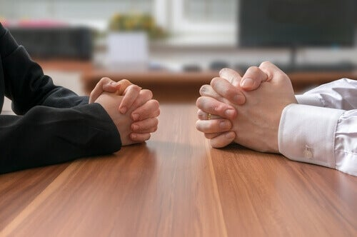 Persone con mani giunte sul tavolo