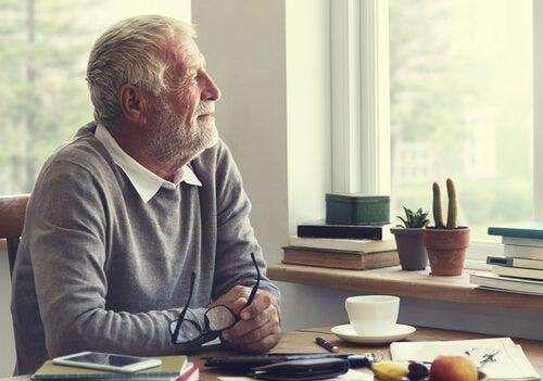 Uomo anziano seduto che guarda dalla finestra