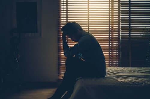 Uomo che piange sul bordo del letto