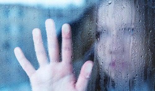 Ragazza dietro una finestra bagnata