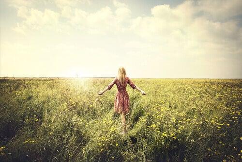 Donna in mezzo a un campo di fiori