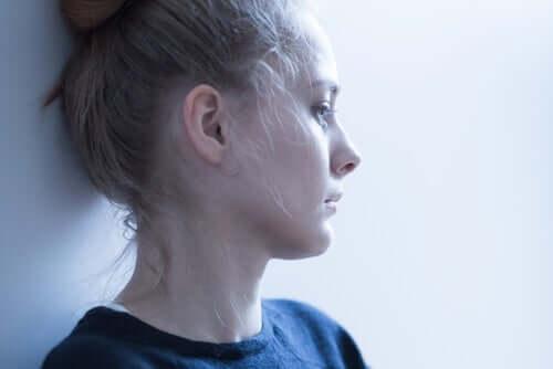 Donna pensierosa appoggiata al muro