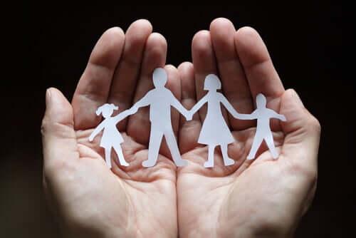 Mani con famiglia ritagliata nella carta