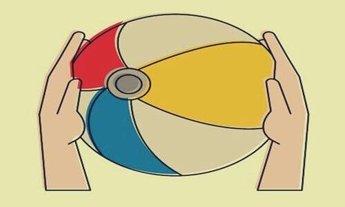 Metafora del pallone in spiaggia, pallone colorato tra due mani