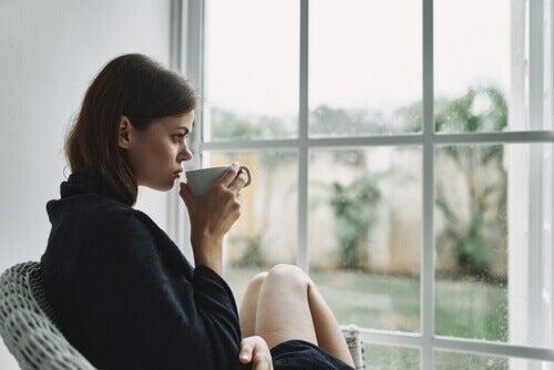 Ragazza che beve un tè in solitudine