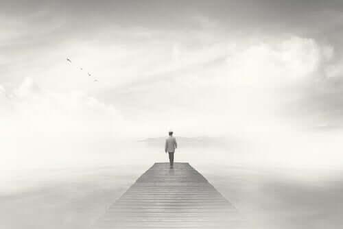 Uomo su ponte sospeso tra le nuvole