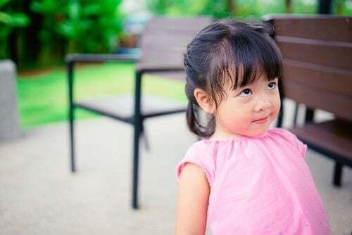 Bambina che fa una smorfia al parco.
