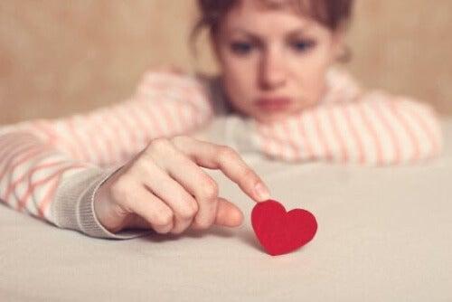 Donna preoccupata che gioca con un cuore.
